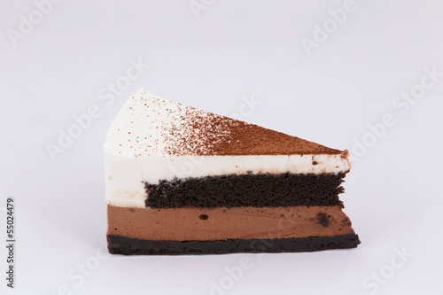 Piece of chocolate cake with coco on white isolated background
