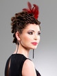 Woman with fashion hairstyle with red feather in hairs
