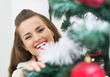 Smiling young woman looking out from christmas tree