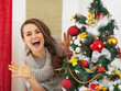 Happy young woman looking out from christmas tree