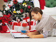 Happy woman with credit card using laptop near christmas tree