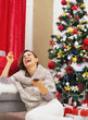 Laughing young woman with tv remote control near christmas tree
