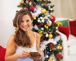 Happy woman in pajamas near christmas tree drinking hot beverage