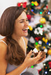 Happy young woman in pajamas having snack near christmas tree