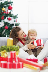 Happy mother showing baby christmas present box