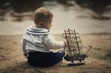little funny boy with ship on coast of river