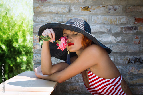 Sexy romantic woman in hat smell flower