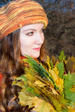 Beautiful fall woman. Portrait of girl  with maple autumn leaves