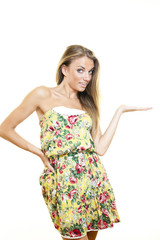 Young smiling beautiful woman with fashion dress showing product