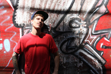 Rapper leaning on a Wall.