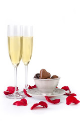 Rose petals, champagne and chocolates on white background