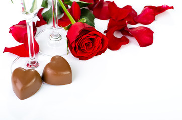Rose petals and chocolates on a white background close up
