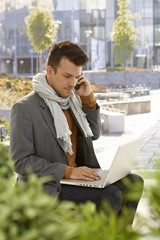 Young man with mobile and laptop outdoors