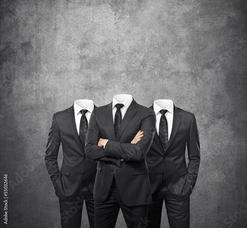 Group of businessmen without heads on concrete background