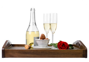 Rose, champagne and chocolates on a wooden tray