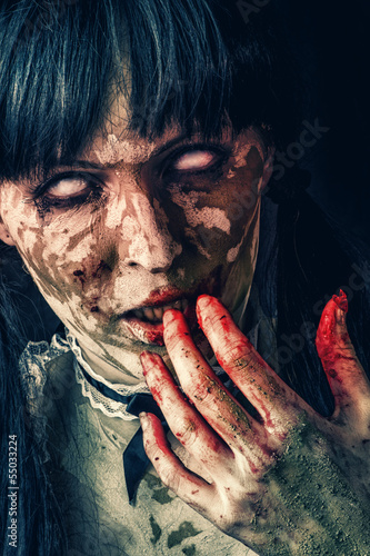 Scary zombie woman with bloody eyes
