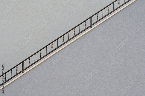 House wall with metal railing of staircase