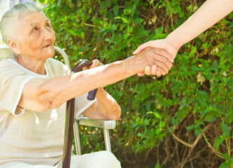 young woman's helping hand towards a very old woman