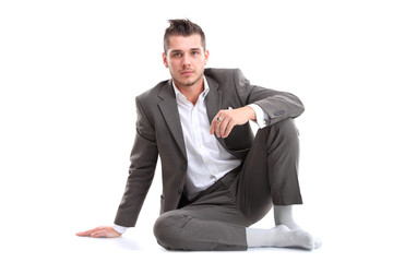 Portrait of business man sitting on the floor isolated
