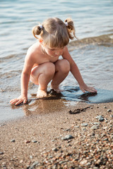 Pretty little girl playing on the seashore