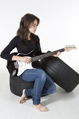 A girl is sitting on a tire and playing electric guitar