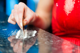 Young woman snorting cocaine in club or bar