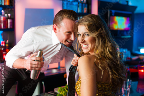 Woman dragging barkeeper in club or bar