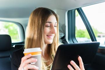 Frau fährt in Taxi mit Kaffee und Tablet Computer
