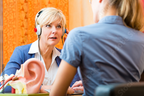 Leinwandbild Motiv Schwerhörige Frau macht einen Hörtest