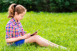 Teenager girl sitting with tablet and surfing the Internet