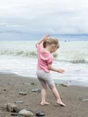 Funny little girl playing at the seaside