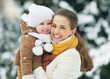 Portrait of smiling mother and baby in winter park