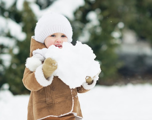 Baby holding big snowball