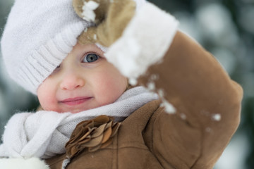 Portrait of happy baby looking out from hat in winter park