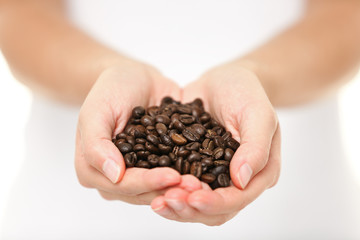 Coffee beans - woman showing coffee bean handful