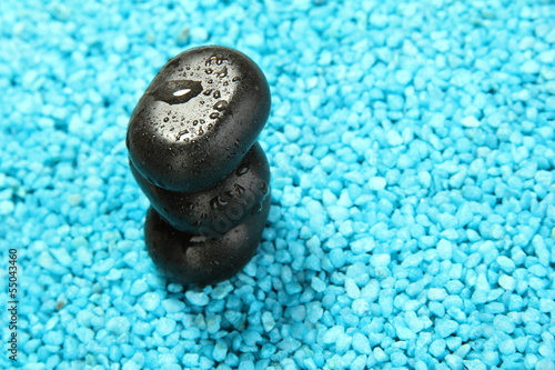 Black stones on blue crystals of sea salt background