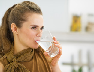 Young housewife drinking water in kitchen