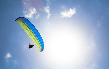 Paraglider hovers in a sunny blue sky