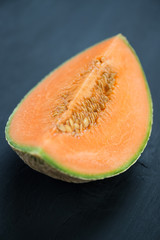 Slice of ripe rockmelon on dark wooden background, vertical shot