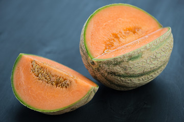 Fruits: rockmelon on dark wooden background, studio shot