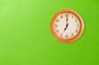 Leinwanddruck Bild - Clock showing 7 o'clock on a green wall