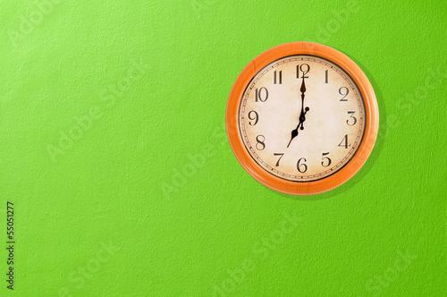 Leinwanddruck Bild Clock showing 7 o'clock on a green wall