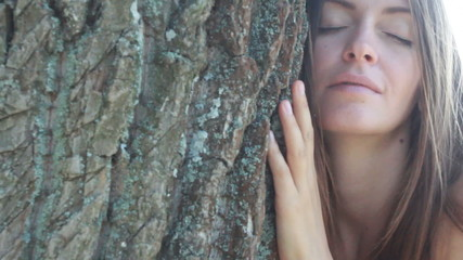 Happy beautiful girl hugging big tree in park