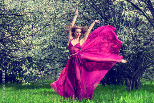 Woman in airy crimson dress dancing among the blossoming trees