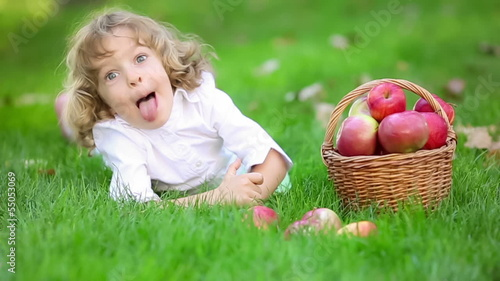 Happy child with red apples in autumn park