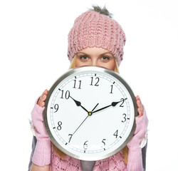 Teenager girl in winter hat and scarf hiding behind clock