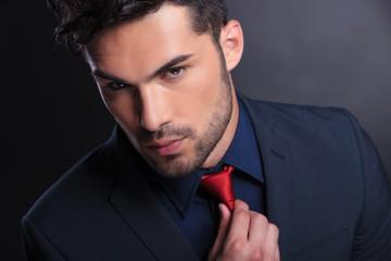 business man fixes his tie