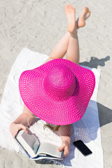Young woman with big pink hat reading on the beach