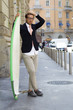 Young man walking in the city with surfboard - needs vacations