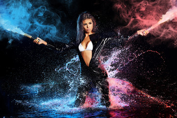 beautiful sexy girl holding gun in water. smoke background